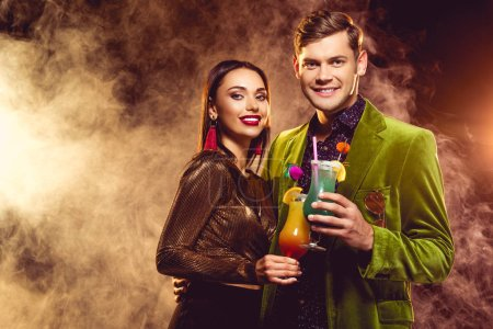 happy glamorous boyfriend and girlfriend clinking with cocktail glasses on party with smoke