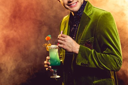 cropped view of man holding sweet alcohol cocktail on party with smoke