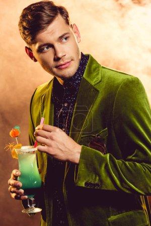 Photo pour Bel homme en veste verte détenteurs d'alcool cocktail à partie avec de la fumée - image libre de droit