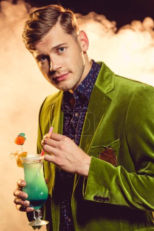 handsome glamorous man in green jacket holding glass with cocktail on party with smoke
