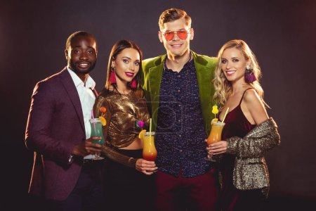 smiling glamorous multiethnic friends with alcohol cocktails on party