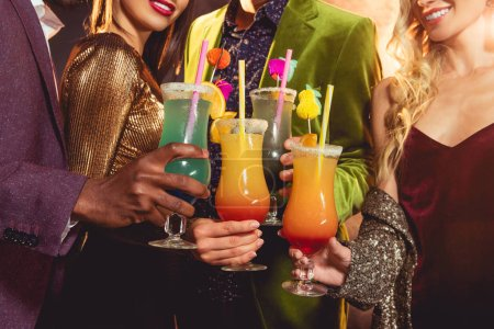 Photo for Cropped view of friends holding alcohol cocktails on party - Royalty Free Image