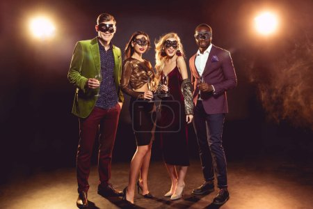 glamorous multicultural friends in carnival masks holding champagne glasses on party with back light