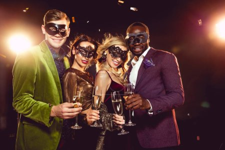 Photo for Luxury multiethnic friends in carnival masks celebrating new year with champagne glasses - Royalty Free Image