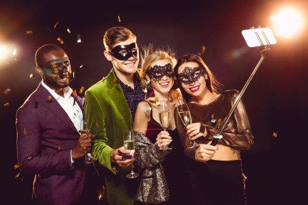 glamorous multicultural friends in carnival masks taking selfie on smartphone