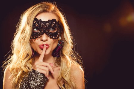 attractive blonde woman in carnival mask with silence gesture