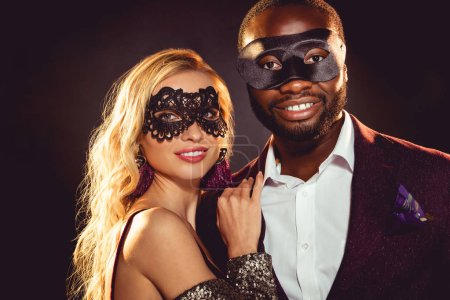 glamorous multiethnic smiling couple in carnival masks for new year party