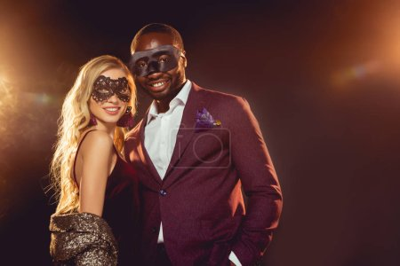 happy multicultural couple in carnival masks for new year party