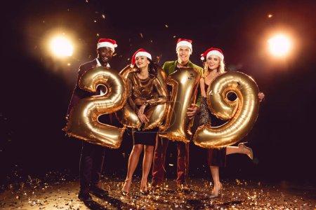 Photo pour Amis heureux en chapeaux santa holding 2019 nouvel an or ballons confetti - image libre de droit