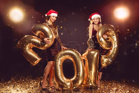 attractive girls in santa hats posing with 2019 new year balloons on golden confetti