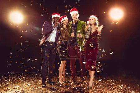Photo pour Amis multiculturels dans chapeaux Santa tenant des verres de champagne et posant sur des confettis avec contre-jour - image libre de droit