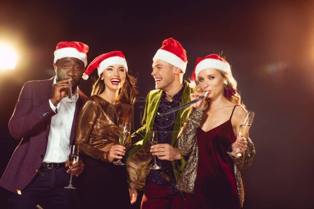 excited multicultural friends in santa hats with champagne glasses