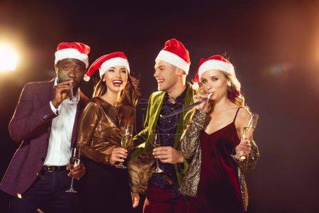 Photo pour Heureux amis multiculturelles en chapeaux santa avec verres de champagne - image libre de droit