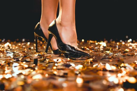 cropped view of woman in black high heels standing on golden confetti