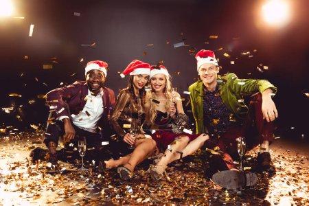 amigos felices del multiculturales con sombreros de santa sosteniendo copas de champagne y sentado en confeti