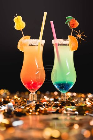 glasses with colorful cocktails with straws on golden confetti for celebration