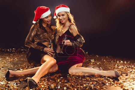 beautiful women in santa hats with champagne glasses sitting on confetti on new year party