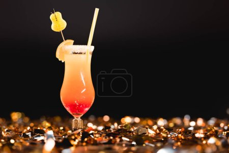 Photo pour Cocktail sucré avec de la paille sur des confettis dorés sur fond noir avec l'espace de la copie - image libre de droit