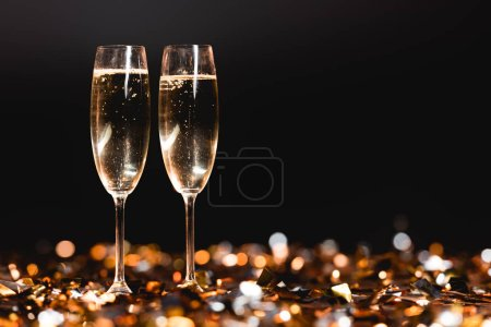Photo for Champagne glasses on golden confetti on black for new year celebration - Royalty Free Image