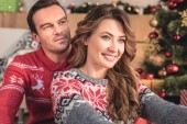 smiling husband and wife looking away at home with christmas tree on background