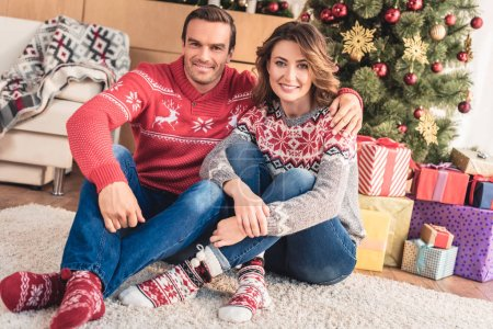 smiling husband and wife looking at camera at home with christmas tree on background