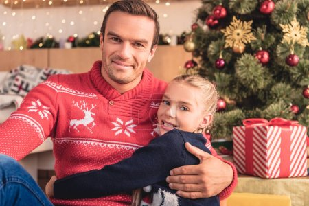 father hugging adorable daughter near christmas tree at home and they looking at camera
