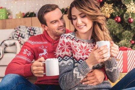 Photo pour Souriant, mari et femme tenant des tasses de cappuccino près de sapin de Noël à la maison - image libre de droit