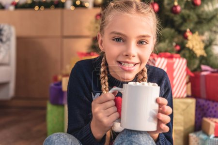 smiling adorable preteen kid holding cup of cappuccino near christmas tree at home and looking at camera
