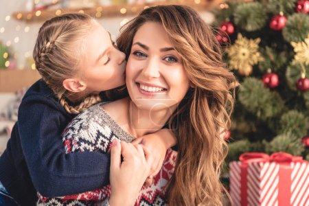 Photo pour Adorable fille baiser mère souriante près d'arbre de Noël à la maison - image libre de droit