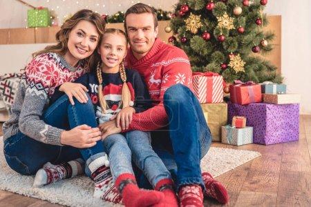 Photo pour Parents et fille étreindre et assis près de sapin de Noël et des cadeaux à la maison, en regardant la caméra - image libre de droit