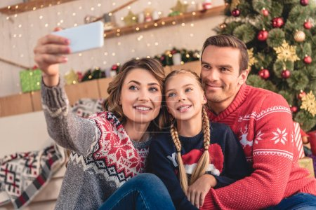 parents and daughter taking selfie with smartphone near christmas tree at home