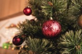 selective focus of christmas tree with red baubles in room