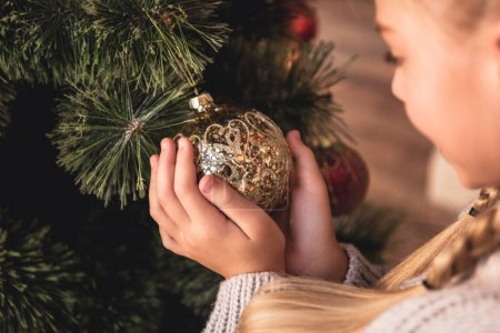 cropped image of adorable preteen kid holding golden bauble in hands at home