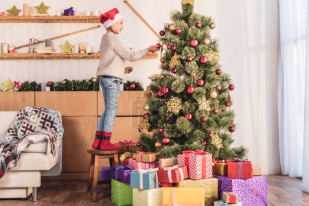 adorable preteen kid in santa hat decorating christmas tree with baubles at home