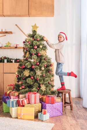 smiling kid in santa hat standing on stool and decorating christmas tree at home with presents