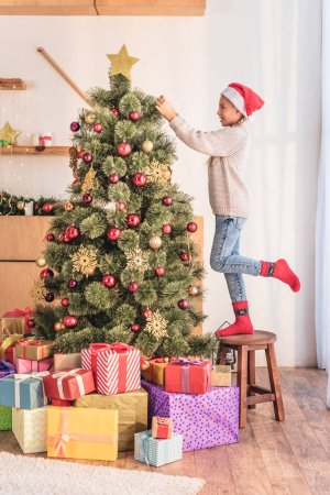 happy child in santa hat standing on stool and decorating christmas tree with gift boxes
