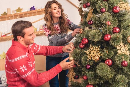 beautiful happy couple decorating christmas tree at home