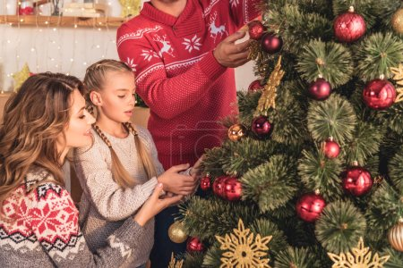 family with daughter decorating christmas tree with balls at home