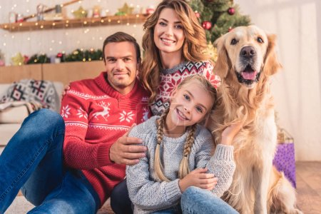 smiling family with golden retriever dog sitting near christmas tree with gifts