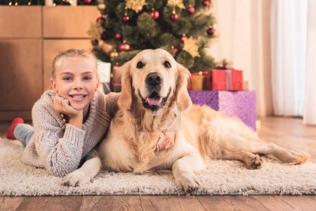 happy kid and golden retriever dog lying near christmas tree with gifts at home