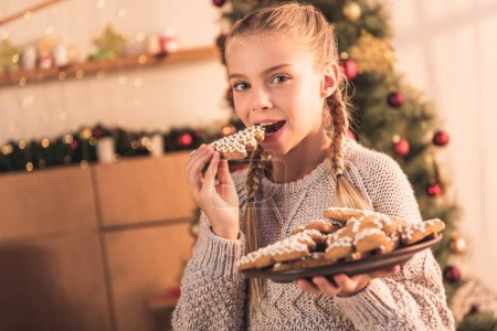 Happy kid eating traditional christmas gingerbread...