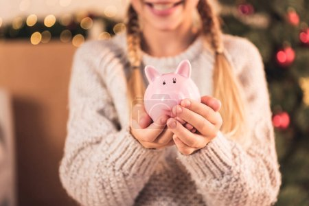 Photo for Cropped view of female youngster holding pink piggy bank - Royalty Free Image