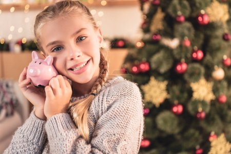 happy kid holding piggy bank at home with christmas tree