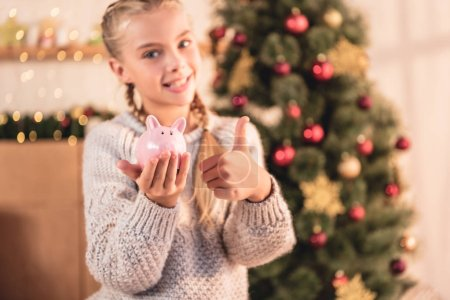adorable child holding piggy bank and showing thumb up at home with christmas tree