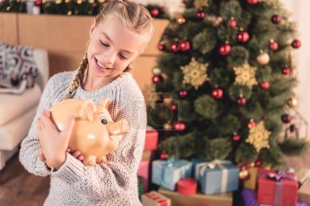 adorable blonde child holding big piggy bank at home with christmas tree