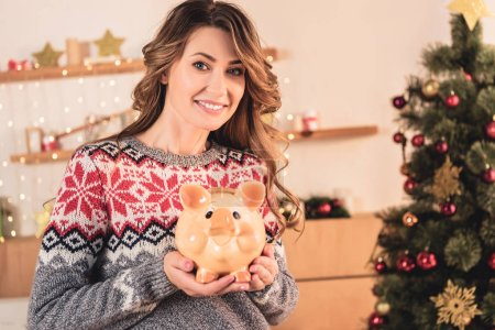 beautiful smiling woman holding piggy bank with savings at home with christmas tree