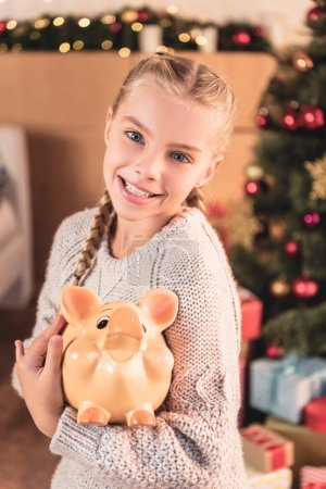 adorable smiling kid holding piggy bank at home with christmas tree