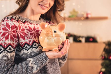 cropped view of woman in christmas sweater holding big piggy bank