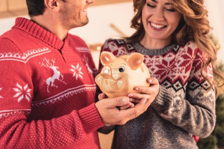 happy couple in christmas sweaters holding big piggy bank