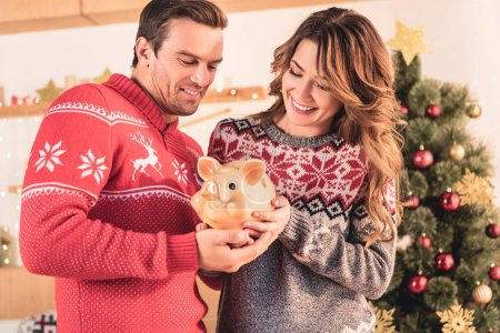 smiling couple holding piggy bank with savings at home with christmas tree